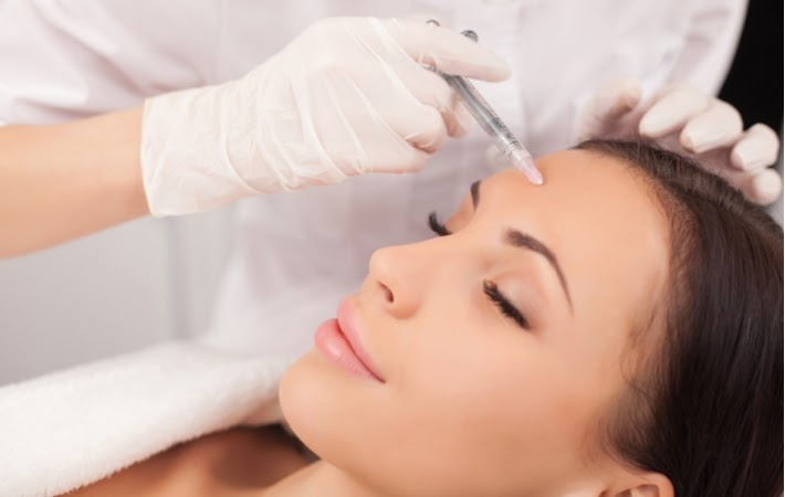 A woman smiling receiving Botox treatment in her forehead to achieve a rejuvenated look