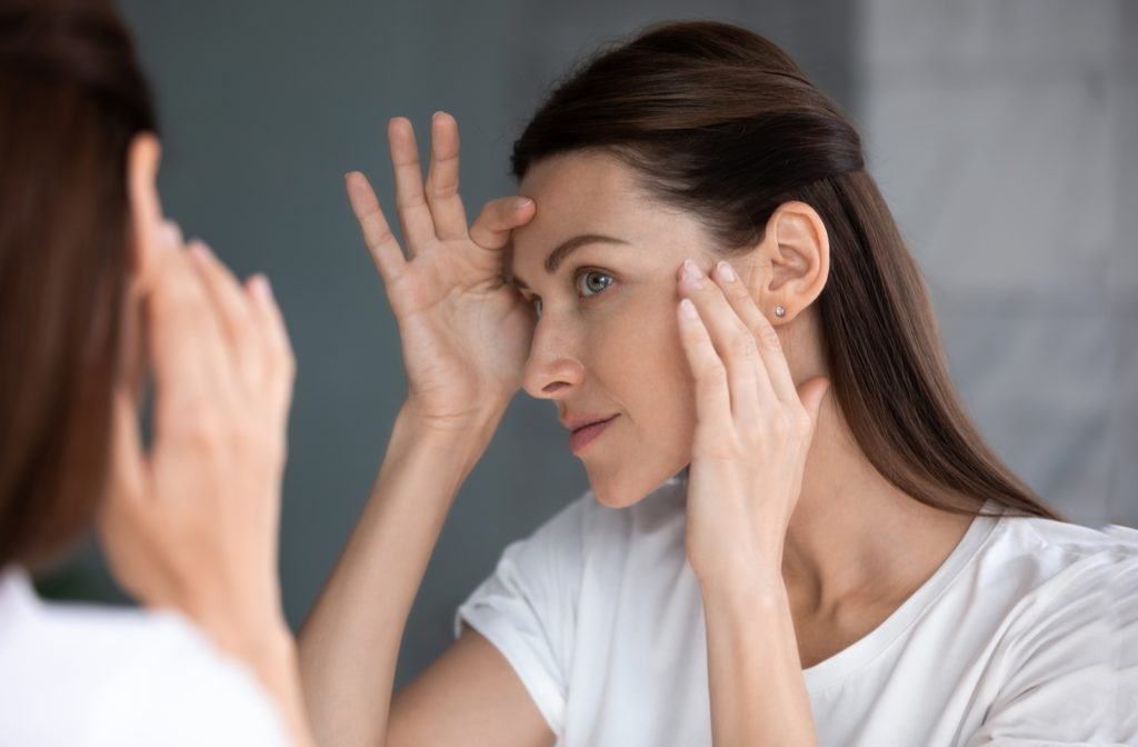 Woman examining her smooth, fuller-looking face in the mirror after a dermal filler